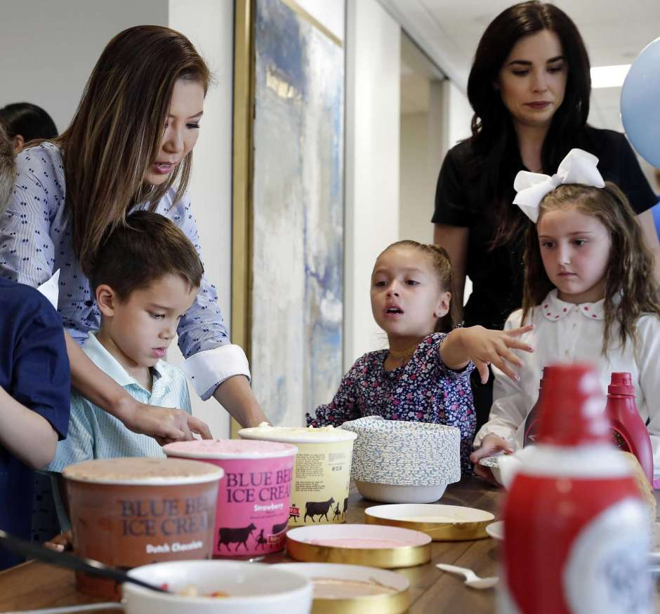 Yuko Vandivere, center, helps her son Nathan, age six, dish up ice cream amid other kids at the monthly team building meeting at ThoughtTrace in their company offices Thursday, Sep. 26, 2019 in Houston, TX.